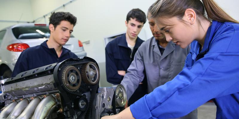 Apprentices repairing a car