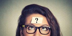 Ein zettel mit Fragezeichen klebt auf der Stirn einer Frau mit Brille