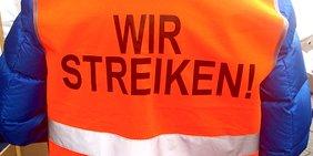 """Rückenseite einer orangenen Warnweste mit der Aufschrift """"Wir streiken"""""""