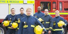 Feuerwhreinsatzteam steht vor einem Feuerwehrauto