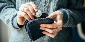 Frau hält Geldbeutel mit einer Münze in der Hand