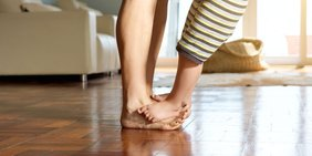 Kinderfüße stehen auf Erwachsenenfüßen