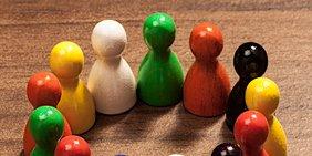 """Nahaufnahme verschiedenfarbiger, im Kreis aufgestellter Spielfiguren im Stil der """"Mensch ärgere dich nicht""""-Figuren"""