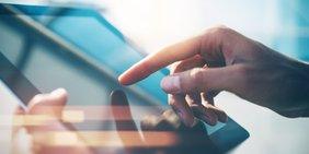 Nahaufnahme: Finger berührt ein Smart-Tablet (Symbolbild für digitale Arbeit / Digitalisierung)