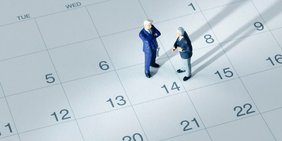 Zwei Miniaturfiguren im Anzug stehen auf einem Kalenderblatt