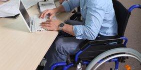 Symbolbild für Behinderte / Schwerbehinderte am Arbeitsplatz und an Unis, Mann im Rollstuhl an Tisch vor Laptop