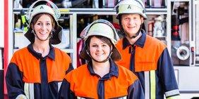 Feuerwehrmann und Feuerwehrfrauen in Uniform vor einem Fahrzeug