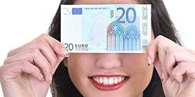 Junge Frau hält sich einen 20-Euro-Schein vors Gesicht und lächelt