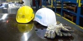 Ein gelber und ein weißer Schutzhelm in einer Industriehalle