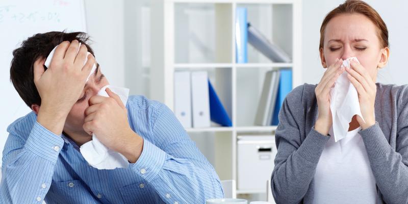 Kranke Beschäftigte im Büro mit Taschentuch