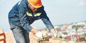 Handwerker mauert in großer Höhe eine Wand