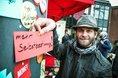 Mann mit Hut an Stellwand an der Uni Duisburg