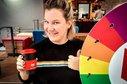 Junge Frau bei Aktion für gute Studienbedingungen mit Glücksrad und Coffee-To-Go-Becher